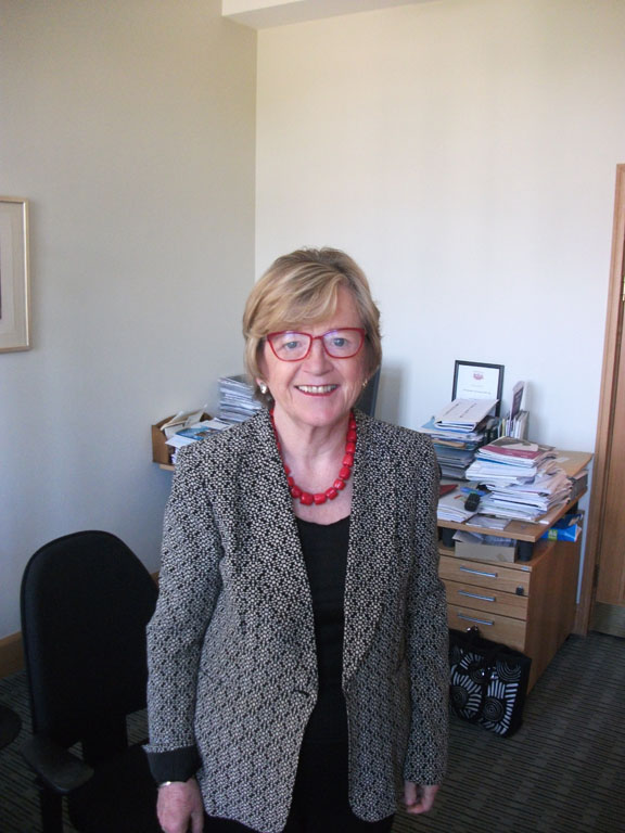 A photograph of Hilary Armstrong standing in an office