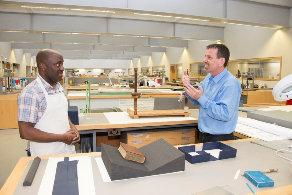 Roger, wearing an apron and standing behind his desk in the conservation studio, is watching Wayne, standing to the right of Roger, as he uses sign language.,