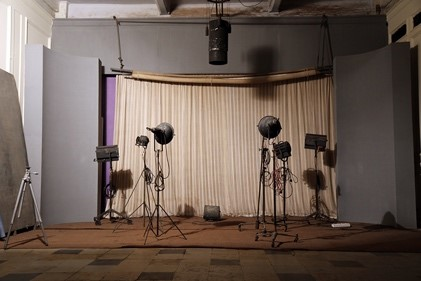 The set up for portrait photograph with several lamps in front of a closed curtain