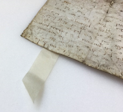 a example picture of a tab of Japanese paper sticking out underneath the parchment. The flwoing script of the charter can be seen, albeit faded in the light.
