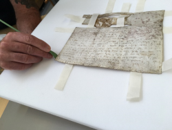 A hand holding a slim green metal conservation spatula, in a similar size to a small paintbrush, is gently pushing the tissue tabs down into cut slits of the white plastazote base which the parchment is resting on. The tab being eased into the cut slit is at the bottom left of the of the parchment.
