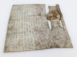 The charter of Henry I, with the brownish seal, is pictured on the new white plastazote base, with the edges of the parchment lying flat against the base.