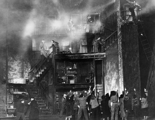 A black and white photo from a performance of One Third of a Nation, depicting the moment when the tenement is on fire - people inside are calling for help while those on the ground are waving up at them.