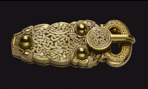 A golden belt buckle, intricately decorated with a web of snakes, predatory birds and long-limbed beasts, discovered at Sutton Hoo.