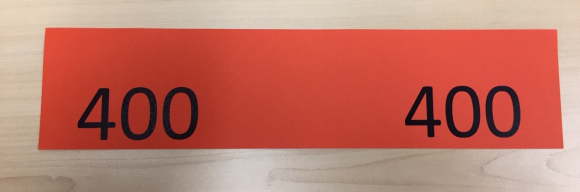 A red piece of paper cut in a long, thin strip with the number 400 listed on each side.