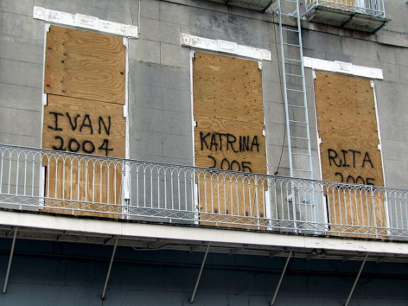 Photograph of an apartment building with three boarded-up doors graffitied with the names Ivan 2004, Katrina 2005 and Rita 2005
