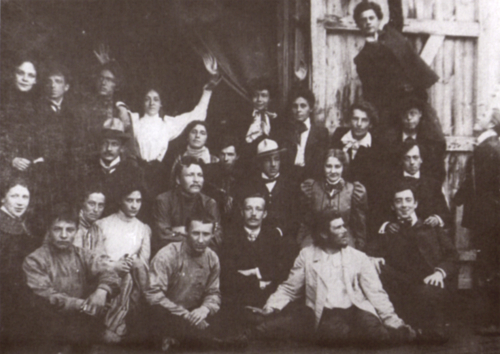 Black and white photo of around 20 members of the Meyerhold Theatre-Studio outside a large building on Povarskaya Street in Moscow; Meyerhold is back row second left.