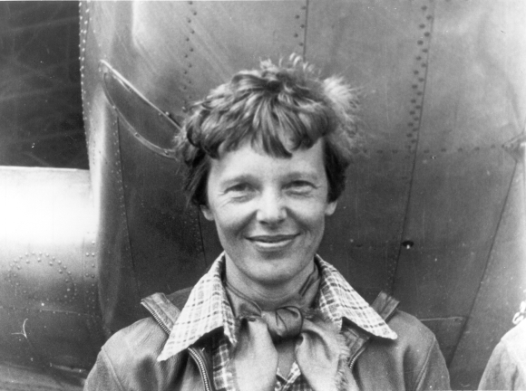 Amelia Earhart standing under the nose of her Lockheed Model 10 Electra plane