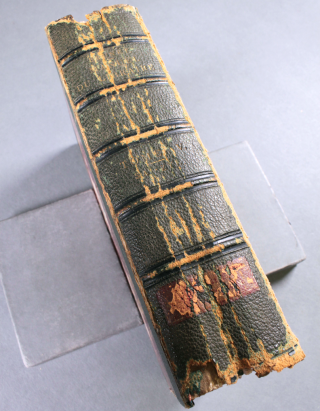 A book, with green leather binding, displaying the damage done to it's spine, as evidenced by cracking running down the length of the spine.