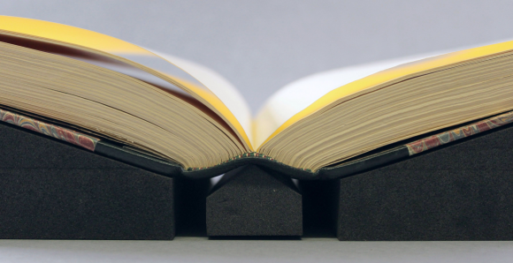 A book lying open, resting on two foam book supports. The spine of the book is also supported by a wedge of the same material.
