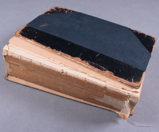 A book in disrepair, showing a complete detachment of the boards (the hard cover of the book, while the spine has disappeared, exposing the text-block.