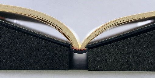 A Rigid Back Book lying open on Foam Supports. The spine of the book is snugly perched within the gap of the two foam supports.