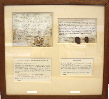 The charters as shown in their original housing, with in a wooden-framed glass mounting. The two charters sit on the top, with the description of each charter below.