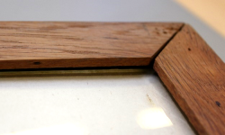 a closeup of the wooden frame corner, showing the frame edges pulling away from each other. the Glass cover edge is also now exposed.