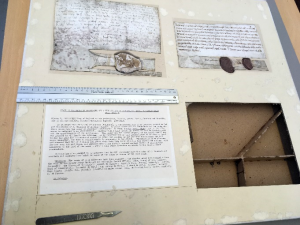 An image of the charter in its original mounting, with one item in the bottom right removed, exposing the backing frame. A metal ruler is lying lengthwise across the mountboard in the middle, and a metal scalpel is also lying lengthwise on the mountboard on the bottom edge.