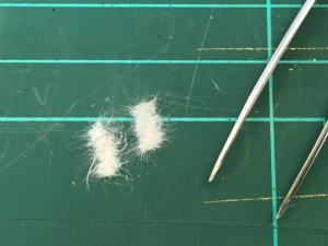 Two pieces of Japanese tissue paper, as seen up close, on a green cutting board, lying next to a set of tweezers. The two pieces of tissue paper are off-white in colour, with very long fibrous edges.
