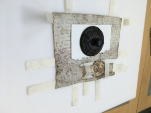 A series of tabs made of Japanese tissue paper attached to the rear of one of the charters. A black weight, sitting on a light board, is keeping the parchment flat.