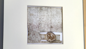 The same charter, still resting on its new white plastazote base, is now seen with a new conservation-friendly mountboard, which has framed the charter. The mountboard is slightly offwhite in colour.
