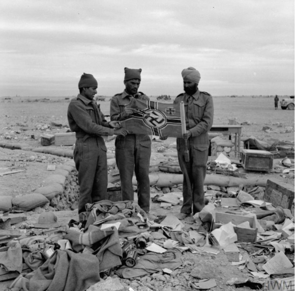 Men of the 4th Indian Division with a captured German flag at Sidi Omar, North Africa