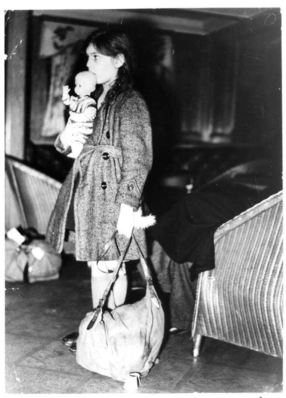 A photograph of a child holding a doll and a bag as she prepares to leave as part of the Kindertransport