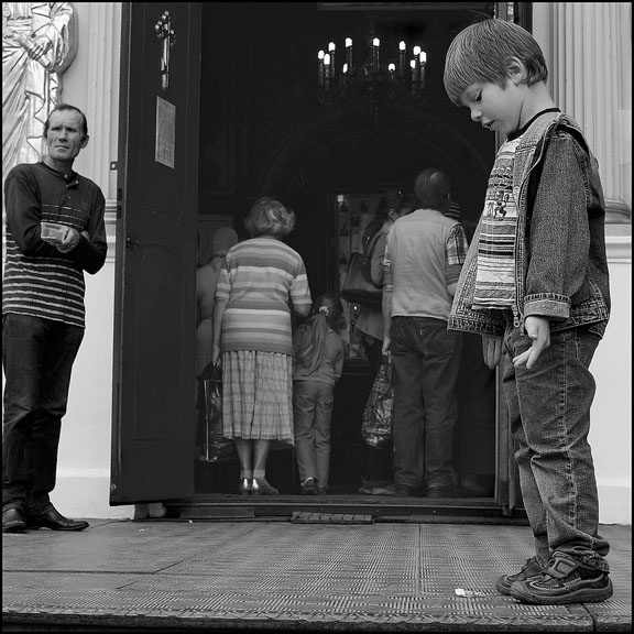 Photograph of a child standing by the entrance to a church as other congregants walk in