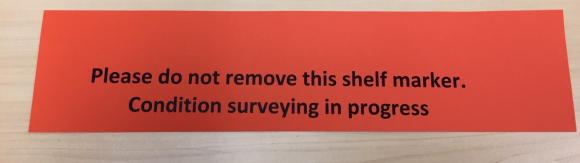 A red piece of paper with text stating 'Please do not remove this shelf marker. Condition surveying in progress.'