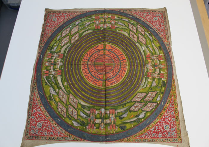 A square piece of cloth which has been painted on. The painting has a circular design of green gardens surrounded by a red floral motif.