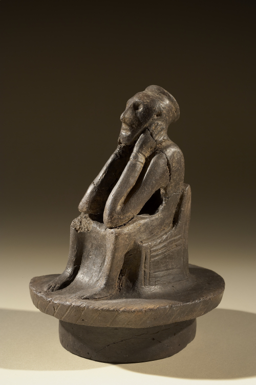 Spong Man, a clay figure seated with its elbows resting on its knees and its hands on either side of its face