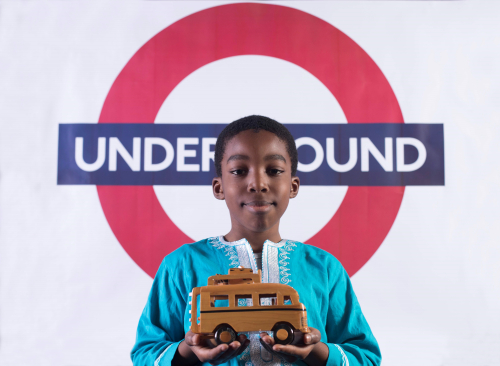 Young boy in African dress in front of London Underground sign holding a toy bus