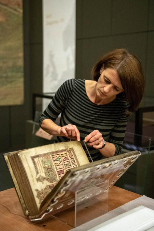 Dr Claire Breay, lead curator of the Anglo-Saxon Kingdoms exhibition, turns the pages of the Lindisfarne Gospels