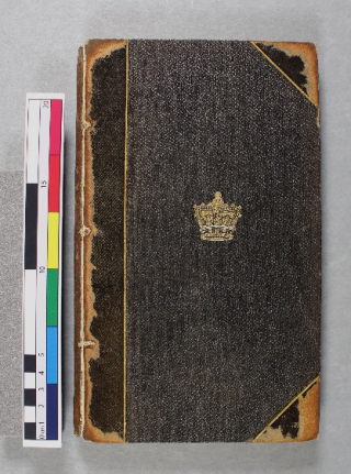 The front cover of a book, bound in black leather with a design of a gold crown in the centre.