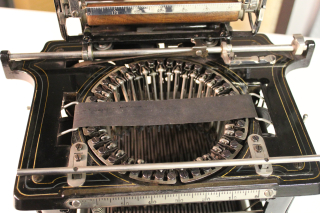 Close-up image of typewriter mechanism showing circle of type bars below ribbon