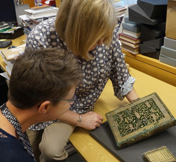 Curators Maddy Smith and Philippa Marks look at a book with an embroidered cover featuring imagery of deer and plants.