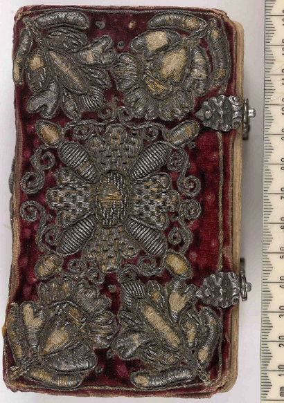 A Danish embroidered binding from the 17th century featuring 3-D floral motifs embroidered in a silver thread against a red velvet background.