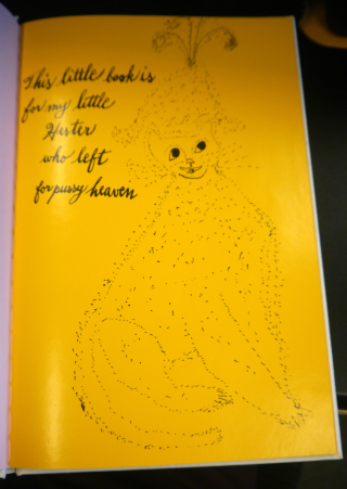 Page opening from the book - a yellow page with black cat illustration