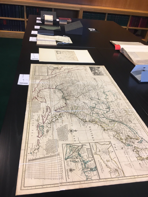 Photo from Indigenous London display showing maps and other items from the collections laid out on a table
