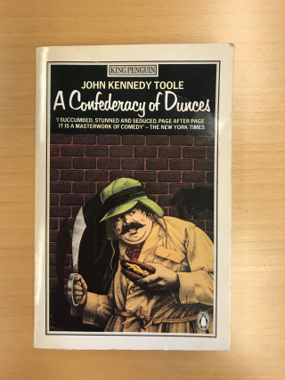 Front cover of A Confederacy of Dunces including illustration of detective with sword in one hand and a hotdog in the other