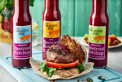 Image of 3 bottles of The Foraging Fox Betroot Ketchup behind  burger land