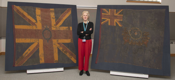 Conservator Liz Rose standing with Royal East India Volunteer colours