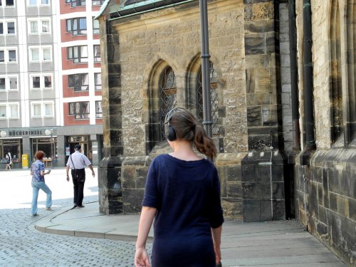 Person standing in front of a church building, they are wearing headphones and listening to a sound walk
