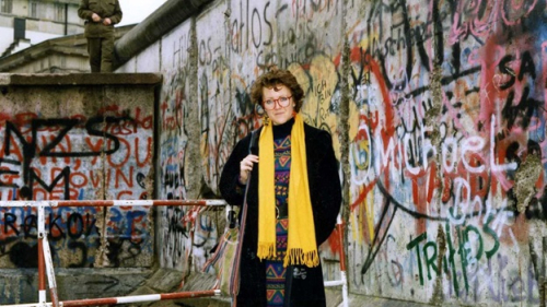 Photograph of Rosie Goldsmith next to the Berlin Wall