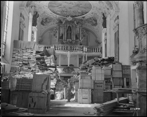 An American soldier amongst cultural property looted by the Nazis and stored in a church at Elligen, Germany in 1945.