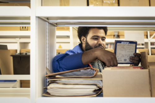 Image of AWATE looking through boxes of cassettes and logs of music in the British Library's basements.