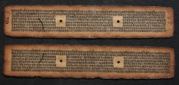 Two long manuscript pages. One placed above the other. Each page has two holes roughly splitting the text into three sections. These holes are used to tie the manuscripts together.