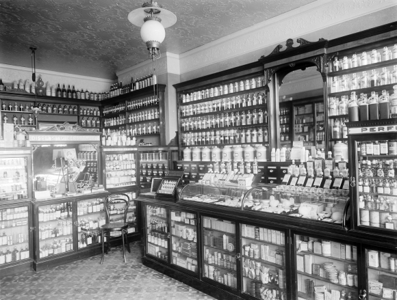 Black & white photograph of the interior of an early 20th century chemists