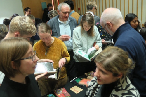 Artists, curators and members of the audience engaging with the artists' books.