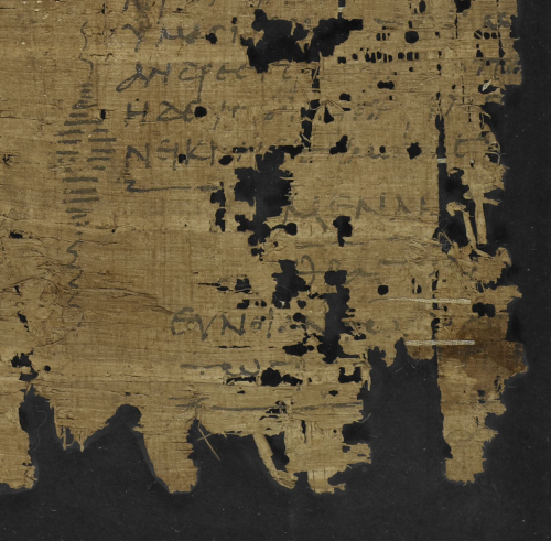 A damaged fragment of ancient papyrus with Greek writing on.