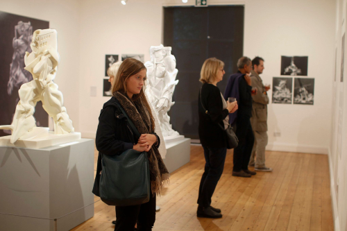 Photograph showing visitors looking at the reconstructed statues shown at the Estorick Collection