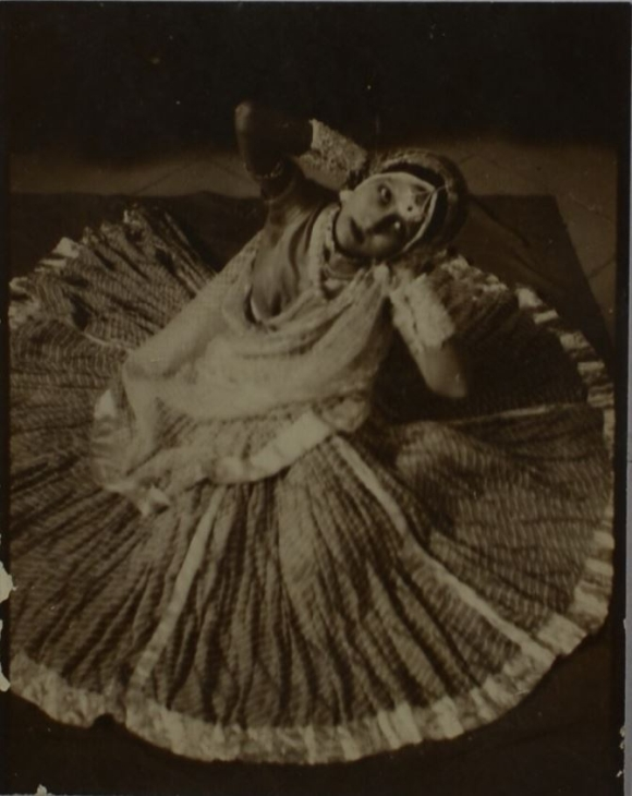Photograph of a dancer sitting with her skirt fanned out on the floor