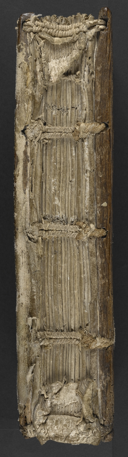 Spine of a book seen straight-on, with visible endband at the top and three lines of sewing supports, evenly spaced and horizontal across the spine, connecting the gatherings of the text block to the boards also visible.